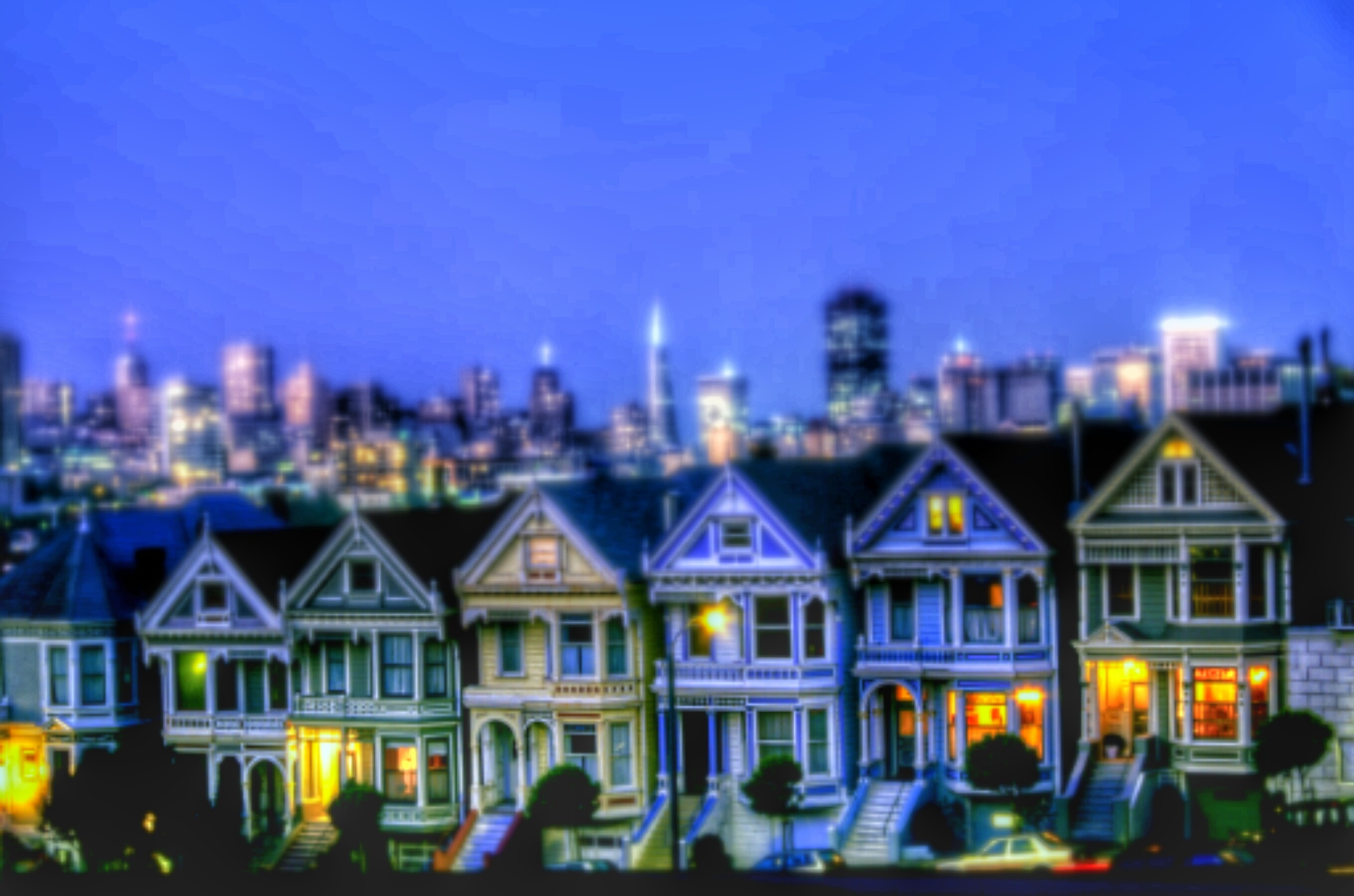 Painted Ladies Houses By Illuminated Urban Skyline Against Sky At Night