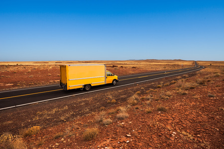 50721214 - yellow moving truck on desert highway, arizona